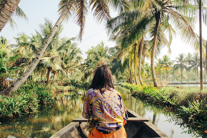 A young woman kayaks through the backwaters of Monroe Island in Kollam District, Kerala, South India.
